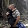 In this image made from video and posted online from Validated UGC, a man carries a child after airstrikes hit Aleppo, Syria, Thursday, April 28, 2016. A Syrian monitoring group and a first-responders team say new airstrikes on the rebel-held part of the contested city of Aleppo have killed over a dozen people and brought down at least one residential building. The new violence on Thursday brings the death toll in the past 24-hours in the deeply divided city to at least 61 killed. (Validated UGC via AP video)