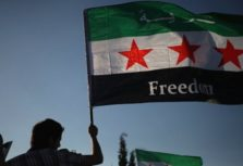 Syrian protester waves the Syrian revolutionary flag, during a protest in front of the Syrian embassy to condemn the alleged poison gas attack on the suburbs of Damascus, during a protest in front of the Syrian embassy, in Amman, Jordan, Friday, Aug. 23, 2013.  Anti-government activists accused the Syrian regime of carrying out a toxic gas attack that is thought to have killed at least 100 people, including many children as they slept, during intense artillery and rocket barrages Wednesday on the eastern suburbs of Damascus that are part of a fierce government offensive in the area.(AP Photo/Mohammad Hannon)