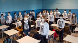 A scuola, nel giorno della memoria, con la pettorina che ricorda il pigiama a righe dei deportati